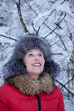 Young cheerful woman in snowy winter forest smiling Royalty Free Stock Photos