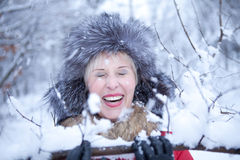 Young cheerful woman in snowy winter forest smiling Stock Images