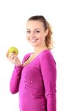 Young cheerful woman in sports wear with apple, isolated over wh Royalty Free Stock Images