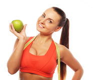 Young cheerful woman in sports wear with apple Royalty Free Stock Photos