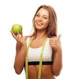Young cheerful woman in sports wear with apple Stock Photos