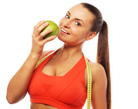 Young cheerful woman in sports wear with apple Stock Photo