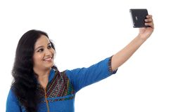 Young cheerful woman taking a selfie against white Stock Image