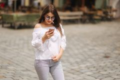 Young cheerful woman watching funny video on smart phone while resting outdoors stock photos