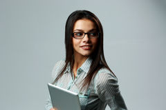 Young cheerful woman wearing glasses, holding tablet computer Stock Image
