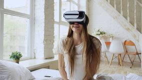 Young cheerful woman wearing virtual reality headset watching 360 VR video movie sitting in the bed at home royalty free stock photography