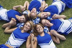 Young Cheerleaders Lying On Field. Group of happy young cheerleaders lying on field forming a circle Stock Images