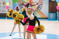 Young cheerleaders perform at the city cheerleading championship. Kamenskoye, Ukraine - March 9, 2017: Championship of the city of Kamenskoye in cheerleading Stock Image