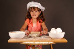 Young chef. A cute young girl rolling out cookie dough, and wearing a chefs hat and apron royalty free stock image