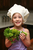 Young Chef. A young girl chef holds some parsley and smiles for the camera Stock Images