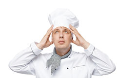 Young chef adjusts his hat on his head on a white Stock Images