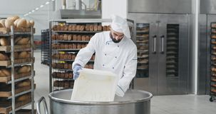Young chef baker with a beard preparing the dough add some more flour in a big container , background bakery worker take. The shelves of baked bread and moving stock video