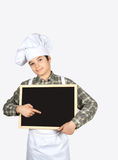 Young chef with blackboard. Child dressed as a chef with blackboard in hand Stock Image