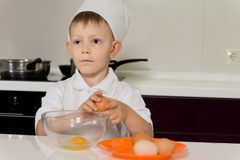 Young chef breaking eggs into bowl Royalty Free Stock Images