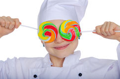 Young chef closed his eyes colored candies Stock Photo