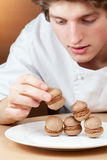 Young chef confectioner puts sponge cakes on plate Royalty Free Stock Images