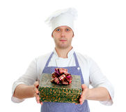 Young chef cook holding present box. Royalty Free Stock Photos