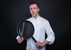 Young chef or cook with knife and pan Stock Photos