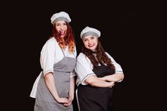 Young chef cook woman black uniform isolated white background apron hat emotion smile two stock image