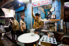Young chef cooks milk with saffron near the street restaurant Royalty Free Stock Photos