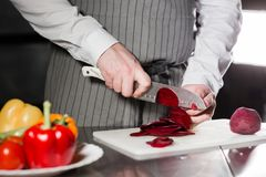 Young chef cutting beet on a white cutting board. Closeup of hand with knife cutting fresh vegetable. Cooking in a Stock Photos