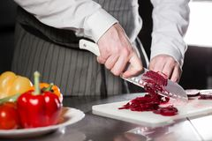 Young chef cutting beet on a white cutting board. Closeup of hand with knife cutting fresh vegetable. Cooking in a Stock Image