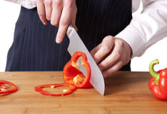 Young chef cutting bell peppers. Royalty Free Stock Images