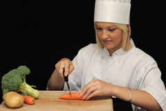 Young chef cutting carrots Stock Image