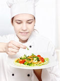 Young chef decorating delicious salad Royalty Free Stock Photo