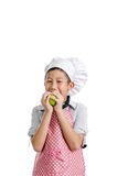 Young chef eating green apple isolated Royalty Free Stock Photos