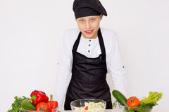 Young chef going to prepare a salad isolated Stock Images