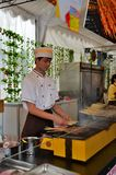 Young chef grills meat and fish on skewers, Singapore Royalty Free Stock Photos