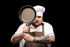 Young chef in hat and apron holding frying pan isolated on black Stock Image