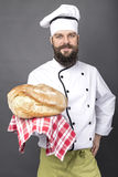 Young chef holding a big rustic bread Stock Photo