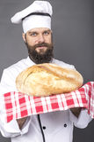 Young chef holding a big rustic bread Stock Image