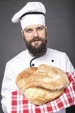 Young chef holding a big rustic bread Royalty Free Stock Images
