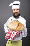 Young chef holding a big rustic bread Stock Photography
