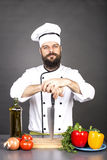 Young chef holding a big sharp knife on a board ready to cook Royalty Free Stock Photo