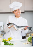 Young chef holding rainbow trout. In professional kitchen stock images