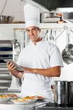 Young Chef Holding Tablet With Pasta Dishes At Stock Photo