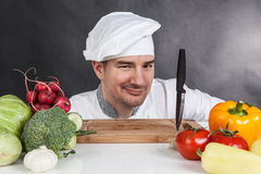 Young chef with knife and vegetable Stock Photos
