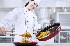Young chef making fried noodle Stock Image