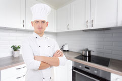 Young chef man in uniform posing in modern kitchen Royalty Free Stock Image