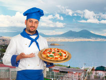 Young chef with neapolitan pizza margherita. With Gulf of Naples in background Royalty Free Stock Photo