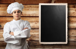 Young chef with panel for menu Royalty Free Stock Image