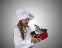 Young chef with pot. Caucasian blond girl with cook costume Stock Image