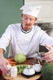 Young chef preparing lunch in kitchen Royalty Free Stock Image
