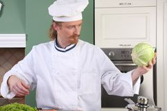 Young chef preparing lunch in kitchen Royalty Free Stock Photography