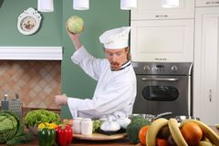 Young chef preparing lunch in kitchen Stock Photos