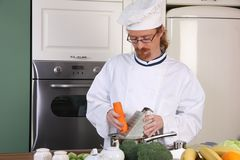 Young chef preparing lunch in kitchen Stock Images